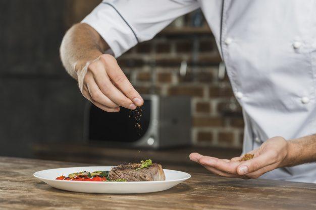 chef-sprinkling-spices-prepared-dish_23-2147863787.jpg